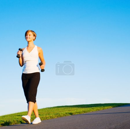 Photo for Young woman walking with weights, from a complete series of photos. - Royalty Free Image