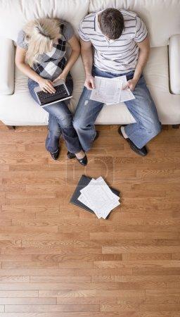 Photo pour Vue d'angle élevé de jeune couple assis sur un canapé avec un ordinateur portable et de la paperasserie. Défroissage vertical. - image libre de droit