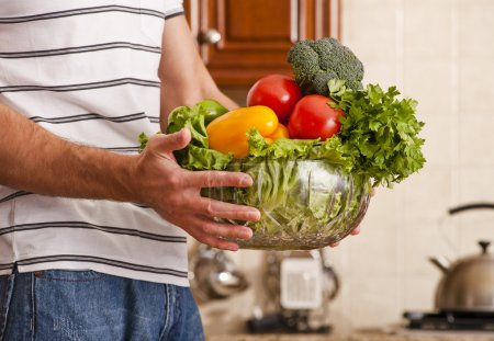 Photo for Man in striped shirt holding a bowl of vegetables in kitchen. Horizontal shot. - Royalty Free Image