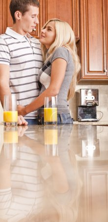 Photo for Young couple smiling at each other with glasses of orange juice on counter. Vertical shot. - Royalty Free Image