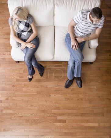 Photo pour Homme et une femme assis lointainement sur les extrémités d'une causeuse de couleur crème. leurs têtes sont détournés de l'autre. Défroissage vertical. - image libre de droit
