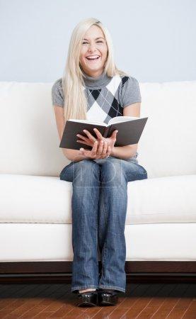 Photo pour Vue complète de la femme heureuse tenant le livre et souriant à la caméra alors qu'elle est assise sur un canapé blanc. Format vertical . - image libre de droit