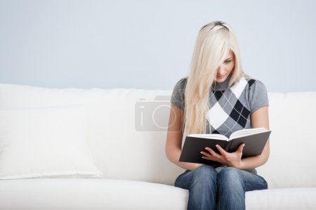 Woman Sitting on Couch and Reading Book