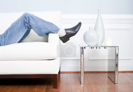 Man's Legs Reclining on White Couch