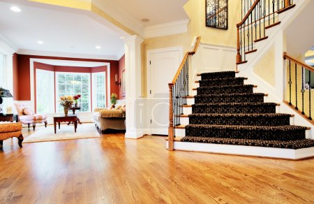 Photo for Open entryway with wood floor and staircase, with view of living room. Horizontal format. - Royalty Free Image