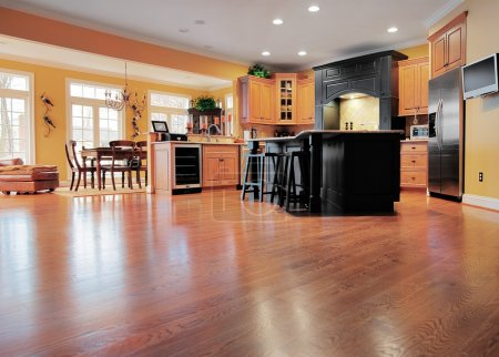Photo for Home interior shows a large expanse of wood flooring in the foreground and a kitchen and dining room in the background. Horizontal format. - Royalty Free Image