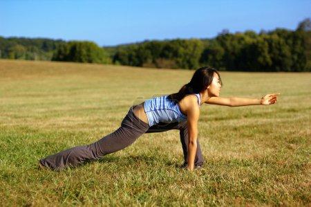 Girl Practicing Yoga In Field