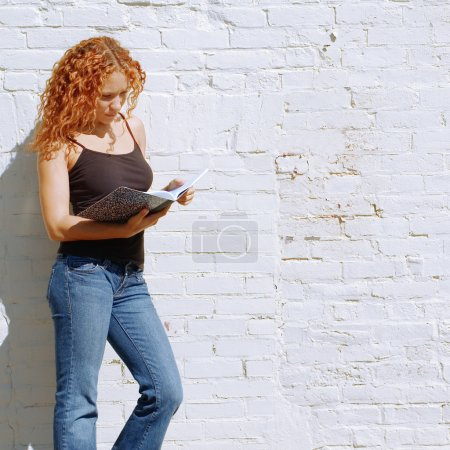 Photo for Attractive urban girl against white brick wall. - Royalty Free Image