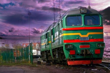 Photo pour Locomotive de fret sur les chemins de fer industriels lettons dans un magnifique coucher de soleil. Nuages de vanille dans le ciel . - image libre de droit