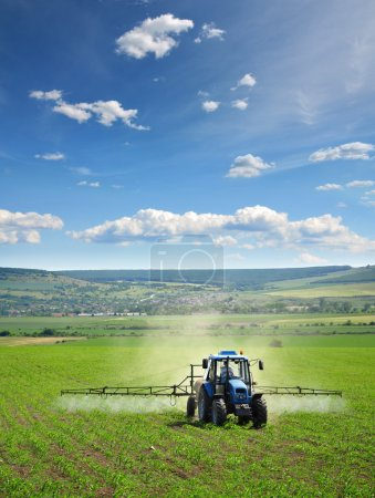 Photo for Farming tractor plowing and spraying on field - Royalty Free Image