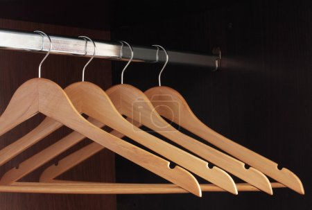 Photo for Wooden hangers hanging in an empty closet on the upper - Royalty Free Image