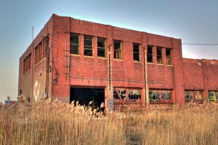 Photo pour Entrepôt de la brique abandonnée entouré d'herbe envahissante - image libre de droit