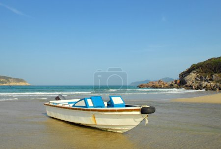 Blue rowing boat on shore