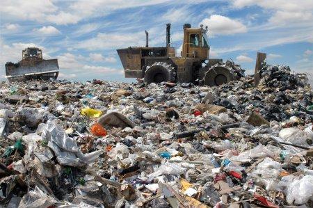 Photo pour Le bulldozer enterre les déchets alimentaires et industriels - image libre de droit