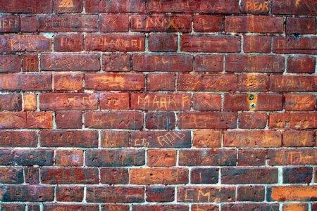 Photo pour Taggé signatures sur un mur de briques urbain. - image libre de droit