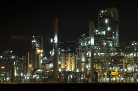 Photo for The converters, pipes, tubes chimneys and structures of a illuminated petrochemical plant at night - Royalty Free Image
