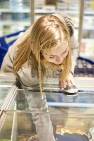 Photo for Young woman reaching in a freezer of the frozen food section of a supermarket, shallow Depth of field, focus on the eyelids - Royalty Free Image