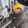 A male maintenance engineer at work on an industri...