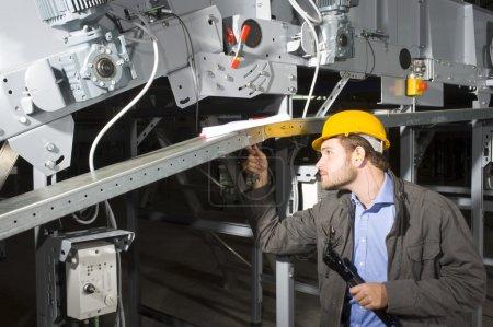 Photo pour Un technicien d'entretien au travail, serrage des boulons d'un appareil industriel - image libre de droit