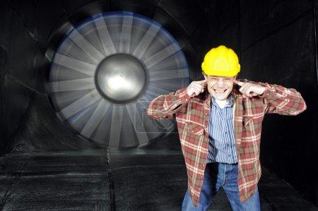 Photo pour Un ingénieur, couvrant ses oreilles pour les protéger contre le bruit d'un wintunnel à l'essai - image libre de droit
