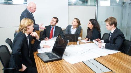 Photo pour Le patron de toute attention à lui-même lors d'une réunion de l'équipe de conception de dessin, discutant des bleus et architecte plans - image libre de droit
