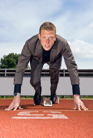 Photo for Young businessman wearing a suit in the starting blocks to start building his career - Royalty Free Image