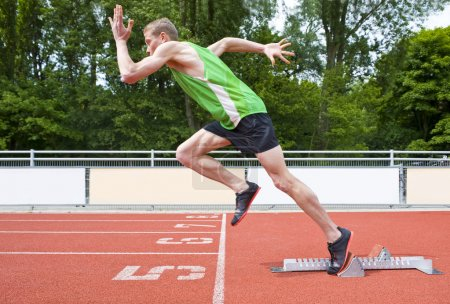 Photo for Explosive start of an Athlete leaving the starting blocks on a sprint run - Royalty Free Image