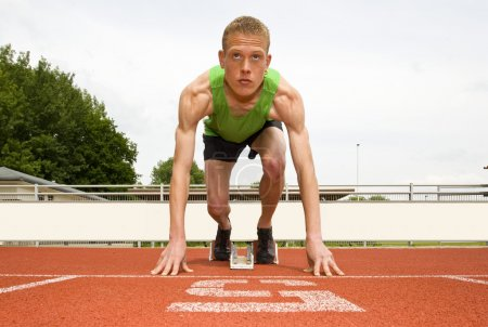 Photo for Athlete in lane five, set to start in the starting blocks for a sprint run - Royalty Free Image