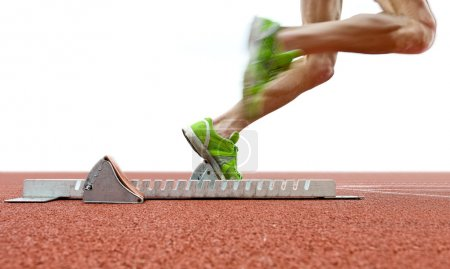 Photo for Action packed image of an athlete leaving the starting blocks for a sprint run on a track - Royalty Free Image