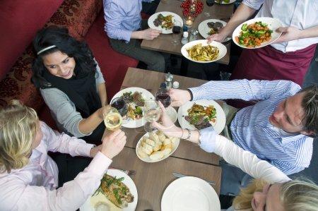 Photo pour Un groupe d'amis dînant dans un restaurant - image libre de droit