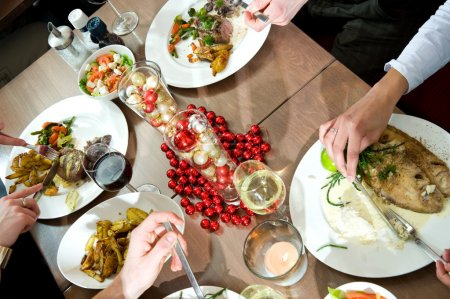 Photo for Meals being eaten on a restaurant table decorated for christmas - Royalty Free Image