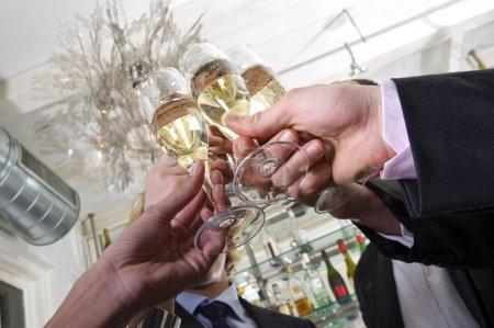 Photo pour Plusieurs mains grillage avec champagne Sylvestre - image libre de droit