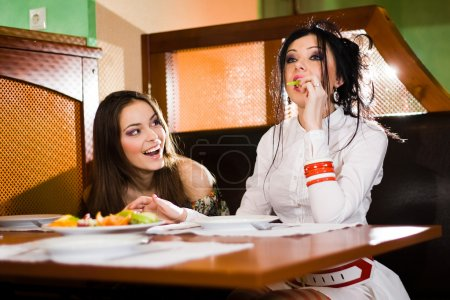 Two beautiful girls at table