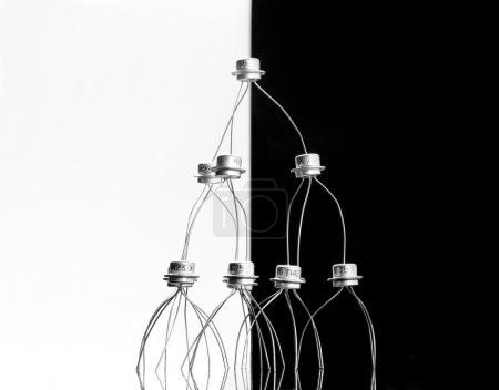 Photo for Concept of transistors acrobats pyramid on black and white - Royalty Free Image
