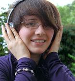 Usmívající se dívka poslouchá hudbu