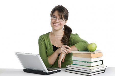 Photo for Young woman looking like a student/teacher, with laptop, stack of books,green apple - Royalty Free Image