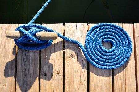 Photo pour Corde bleue enroulée et taquet sur Marina Dock - image libre de droit