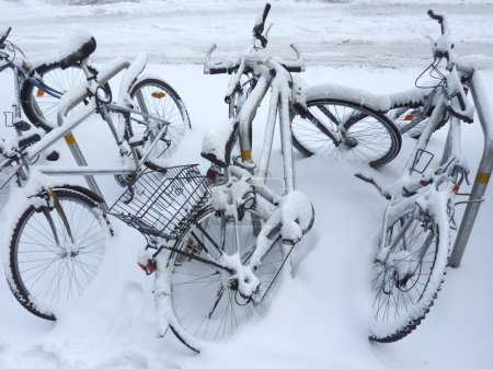 Photo for Several bicycles covered by snow in the street - Royalty Free Image