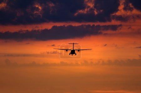 Photo pour Scène de coucher de soleil avec silhouette d'un avion d'atterrissage - image libre de droit