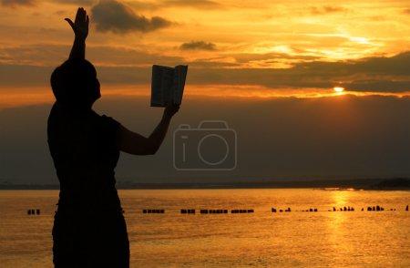 Photo pour Femme priant avec la bible contre le coucher du soleil d'été, personne n'est identifiable - image libre de droit