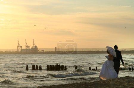 Photo pour Couple marié pendant l'été promenade coucher de soleil sur la plage - image libre de droit