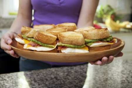 Woman Holding Platter of Egg Sandwiches