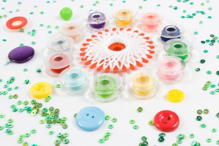 Sewqing bobbins, buttons, beads on white