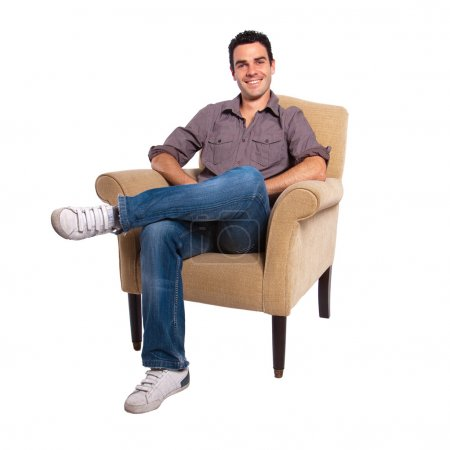 Foto de Retrato de un joven sentado en un sofá sobre un fondo blanco - Imagen libre de derechos