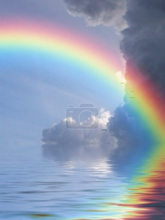 Photo for Rainbow reflected in ocean against a background of clouds - Royalty Free Image