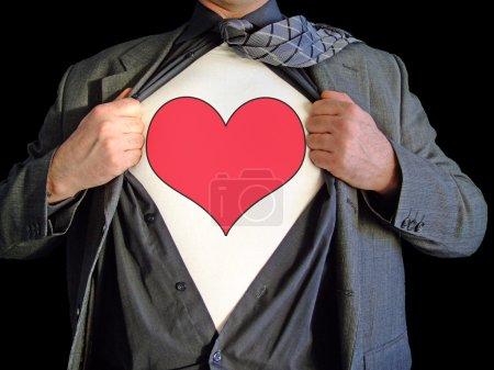 Photo pour Un homme d'affaires isolé sur un fond noir déchirant ouvert sa chemise pour révéler un signe de coeur sur un t shirt - image libre de droit