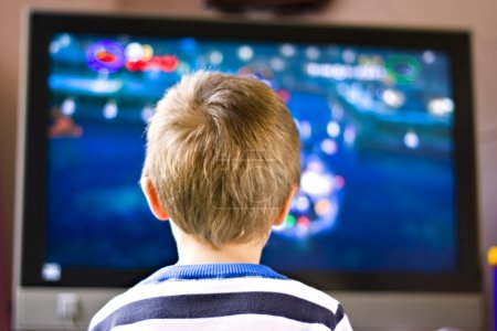 Photo for Candid close up portrait of a cute six year old boy watching television - Royalty Free Image