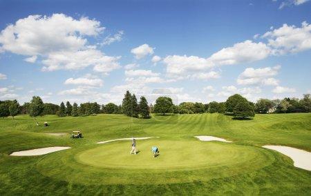 Photo pour Panorama du terrain de golf avec golfeurs et voiturettes - image libre de droit