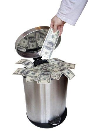 Photo for Wasting money - dollar bills in trashcan - Royalty Free Image