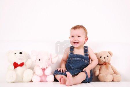 Photo pour Portrait de joli bébé qui rit avec des jouets en peluche - image libre de droit